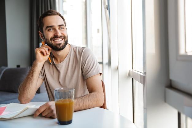 Красивый счастливый умный человек делает заметки, сидя за столом у себя дома