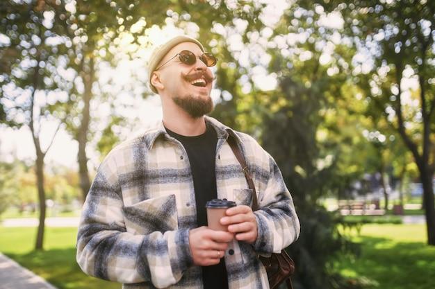 잘생긴 행복 미소 수염 난된 남자는 도시 공원에서 산책 하는 동안 거리 밖에서 커피를 마신다