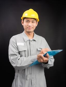 Красивый счастливый руководитель или техник, пишущий заметки, клипборд на черном