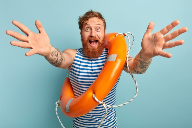 Красивый счастливый удивленный мужчина с оранжевым спасательным кругом в помещении, носит полосатый сине-белый жилет