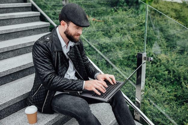 階段で屋外に座ってコーヒーを飲み、ラップトップで作業しているハンサムな幸せな労働者