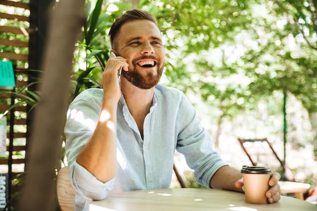 携帯電話で話しているハンサムな幸せな若いひげを生やした男。
