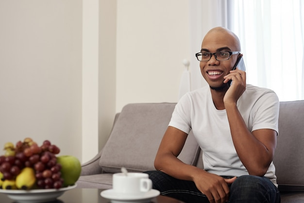 Handsome happy young black man drinking coffee at home and talking on phone with friend or relative