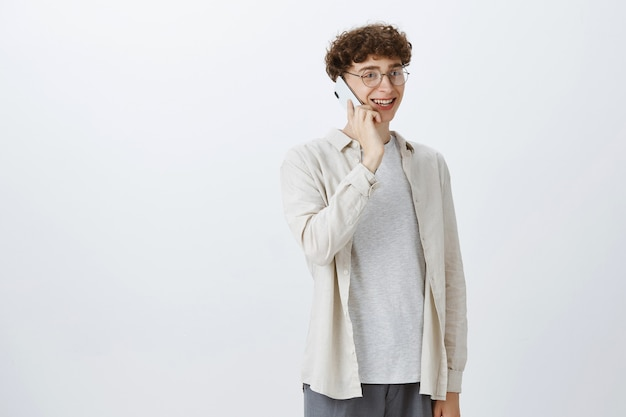 Bel ragazzo giovane felice parlando al telefono cellulare