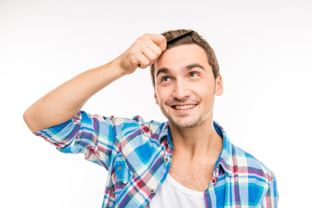 Красивый счастливый молодой человек, расчесывающий волосы