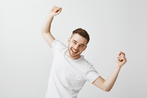 Bel giovane felice che balla in maglietta bianca sul muro grigio