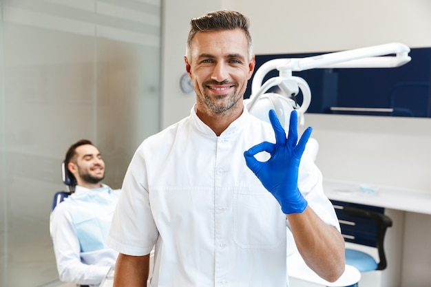 Handsome happy young man doctor in medical dentist center showing okay gesture