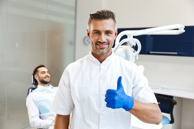 Handsome happy young man doctor in medical dentist center showing thumbs up