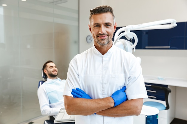 Handsome happy young man doctor in medical dentist center