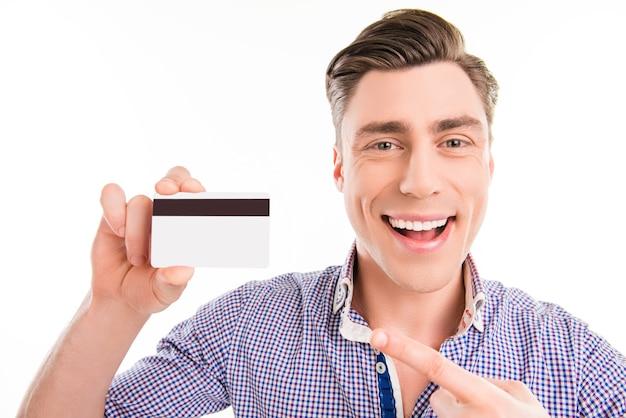 Красивый счастливый молодой человек, указывая на банковскую карту