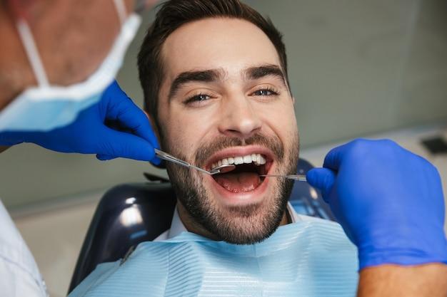 Красивый счастливый молодой человек, сидящий в медицинском стоматологическом центре, глядя на камеру.