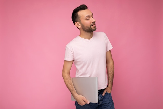 Handsome happy young unshaven man holding laptop computer looking to side in t-shirt on isolated pink background.