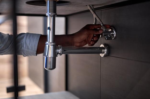 ハンサムな勤勉な配管工がバスルームにシンクをインストールするクローズアップ写真、トリミングされた黒人男性。男はシンクを修理、修理しています。仕事中の熟練した便利屋。側面図