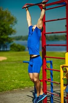 Красивый здоровый счастливый srtong спортсмен мужчина мужчина упражнения в городском парке - фитнес-концепции в прекрасный летний день на турнике