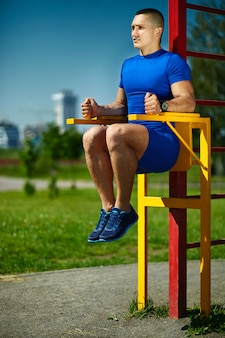 Handsome healthy happy srtong athlete male man exercising at the city park - fitness concepts on a beautiful summer day on horizontal bar