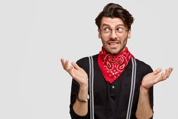 Handsome hesitant guy shrugs shoulders, looks doubtfully aside, doesn`t know what to say, wears stylish shirt and red bandana on neck