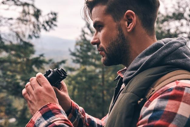 ハンサムなハイカー。森の中に立っている間双眼鏡を通して目をそらしているバックパックを持つ現代の若い男