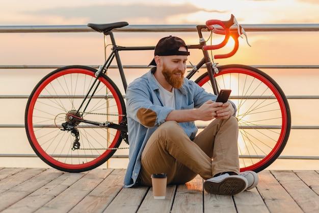 海沿いの朝日、自転車で旅行するスマートフォンを使用してハンサムな流行に敏感なひげを生やした男、健康的なアクティブなライフスタイルの旅行者