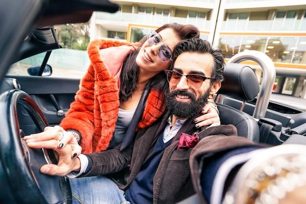 ガールフレンドと楽しんでいるハンサムな流行に敏感なボーイフレンド-車の旅行でselfieを取る幸せなカップル