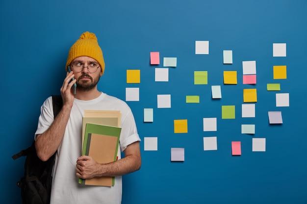 Un bel hipster chiama un amico dopo le lezioni, torna dal college, sta con i libri di testo e lo zaino