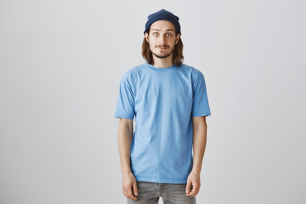 青いtシャツとビーニーでハンサムな流行に敏感な男