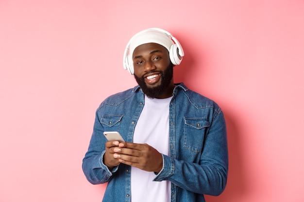 Битник красивый парень в наушниках, довольный, улыбаясь в камеру, слушает музыку в наушниках, используя мобильное приложение, стоя на розовом фоне.