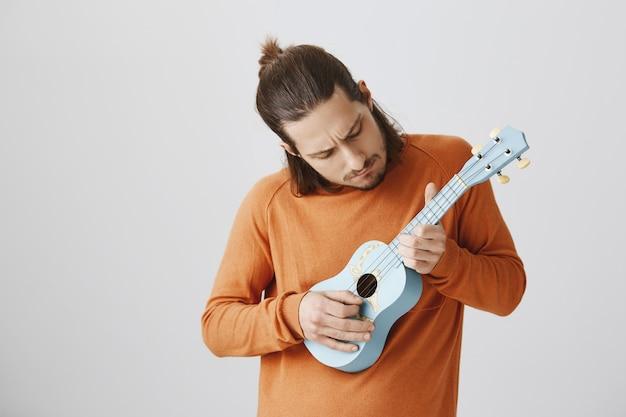 Красивый парень-хипстер учится играть на гавайской гитаре