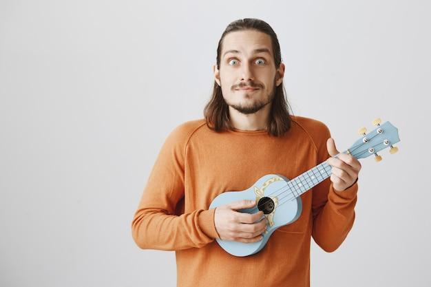ハンサムな流行に敏感な男のウクレレを演奏し、笑顔