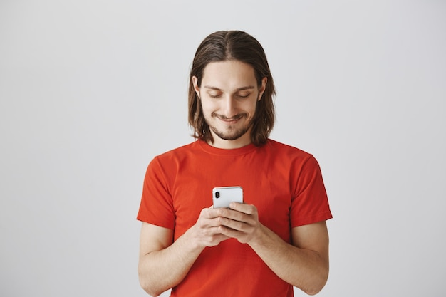 Handsome hipster guy in red t-shirt using mobile phone, messaging
