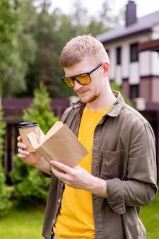 紙の本とお茶を飲みながら公園で休んでいるハンサムな流行に敏感な男、屋外で読んでいる青年実業家のフリーランサーの学生。夏、自己教育、研究、トレーニングコースとプログラムの概念