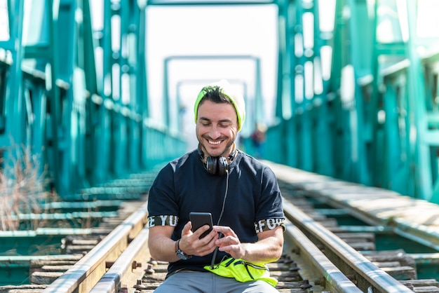 Handsome hipster guy using the cellphone and wearing headphones sitting on the train tracks