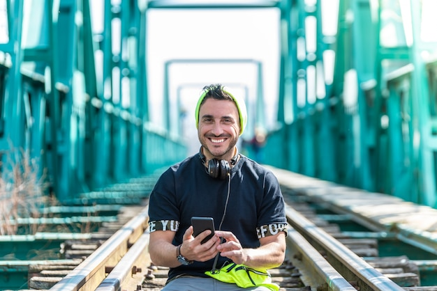 Handsome hipster guy using the cellphone and wearing headphones. sitting on the train tracks.