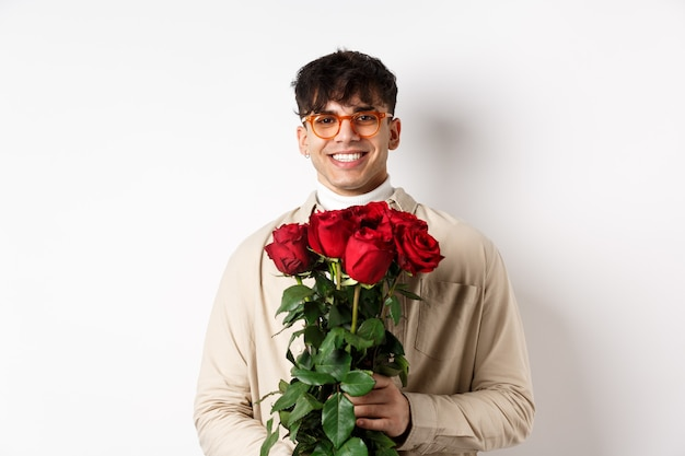 Handsome hipster guy waiting for his lover with bouquet of roses. young man with flowers standing on valentines day over white background.