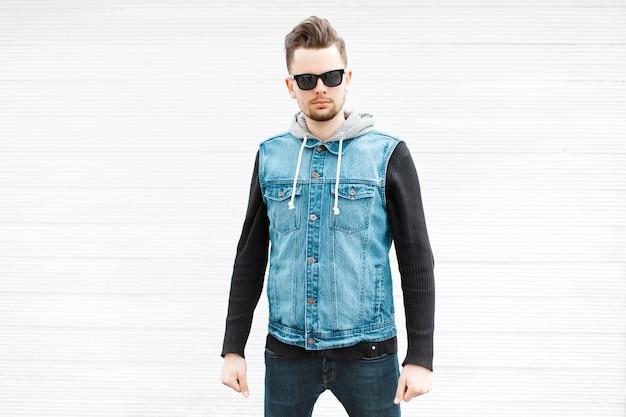 白い木製の壁の近くにサングラスとスタイリッシュなデニムジャケットを持つハンサムな流行に敏感な男