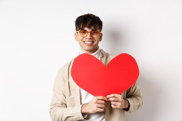 Красивый хипстерский парень в темных очках и сережке, ожидающий настоящей любви в день святого валентина, держит большое красное сердце и улыбается, стоя на белом фоне