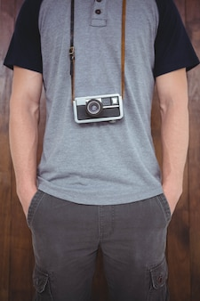 Handsome hipster holding retro camera around hipster neck