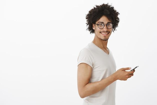 スマートフォンを持って笑顔のメガネでハンサムな流行に敏感な男