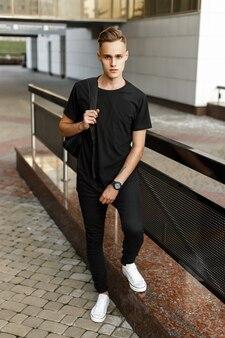 モダンな建物の近くに立っているバックパックとスタイリッシュな黒のtシャツ、ズボン、白いスニーカーのハンサムな流行に敏感な男