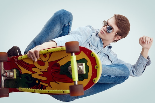 Handsome hipster man in jeans jacket doing the flip on stylish skateboard