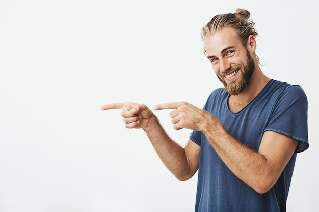 Handsome hipster man pointing with fingers at copyspace