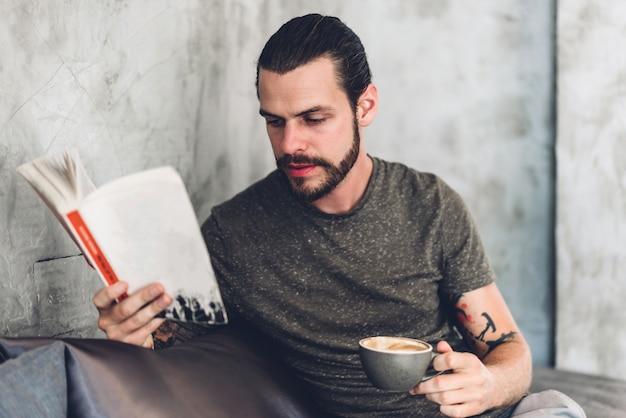 リラックスしたハンサムな流行に敏感な男は、紙の本の仕事の研究を読んで、カフェやレストランで椅子に座っている間にページの雑誌を見て