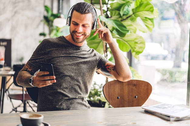 コーヒーを飲みながらデジタルスマートフォンを使用してリラックスし、カフェやレストランのテーブルでメッセージを入力して画面を見て、オンラインゲームやソーシャルメディアで遊ぶハンサムな流行に敏感な男