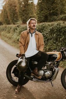 田舎でレトロなオートバイに座っているハンサムな流行に敏感な男