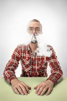 ハンサムな流行に敏感な男が自宅でタバコを吸っています。上向きに見て自由時間を楽しんでいる男。
