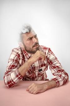 Sigaretta di fumo dell'uomo bello dei pantaloni a vita bassa a casa. uomo che guarda verso l'alto e godendo di trascorrere il tempo libero.