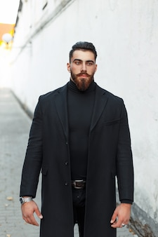 Handsome hipster man with a beard in a black coat on the street