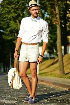 Красивый битник модель мужчина в стильной летней одежде позирует в шляпе с сумкой