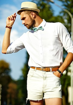 모자에서 포즈 세련 된 여름 옷에 잘 생긴 유행을 좇는 모델 남자