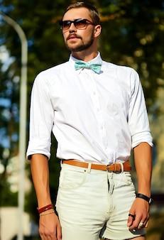 선글라스에 포즈 세련 된 여름 옷에 잘 생긴 힙 스터 모델 남자