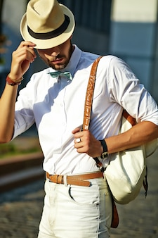 Handsome hipster model man in stylish summer clothes posing  in hat with bag